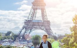 Boy with bunch of colorful balloons in Paris near the...