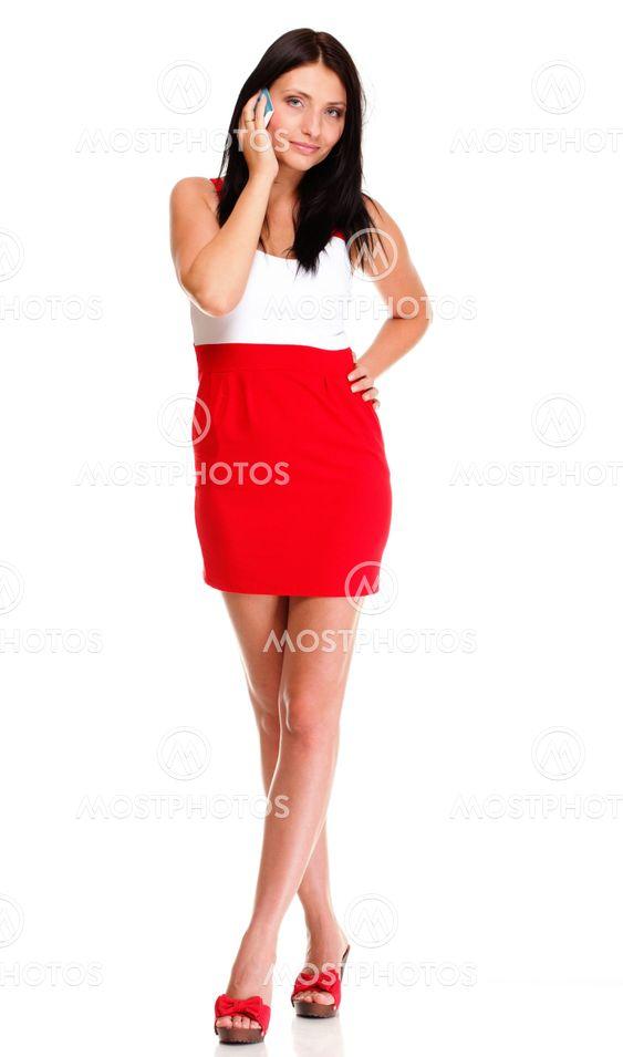 Full length of woman walking talking on mobile phone...