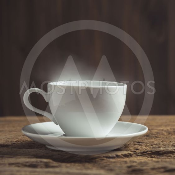 white coffee cup with smoke on wood table