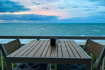 A coffee cup on a table with a vibrant sunrise over the...