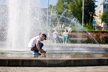 Boy near a splashing fontain in the center of town 12...