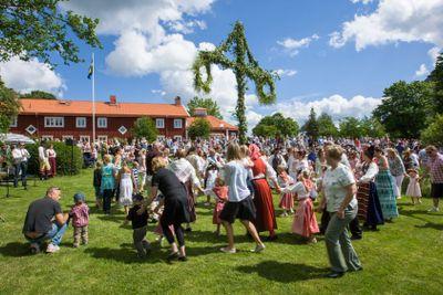 Midsommarfirande med dans runt midsommarstången, Fresta,...