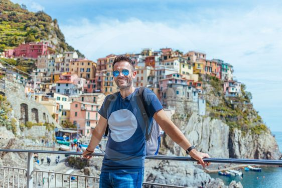 Young man enjoying the view of Manarola in the UNESCO...