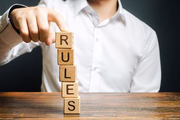 A man holds a tower of blocks with the word Rules from...
