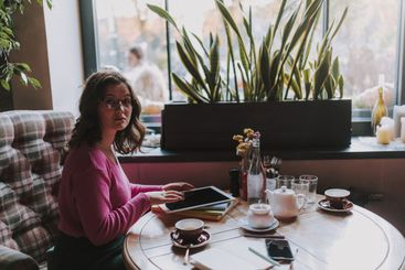 Pretty young lady looking at camera in coffee house