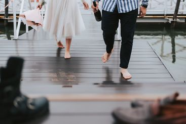 Feet of the newlyweds on the background of the pier.The...