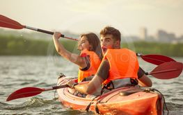 Happy couple kayaking on river with sunset on the...