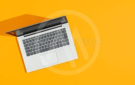 Laptop on a bright yellow desk