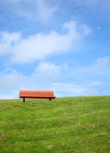 A park bench with a big blue sky and green grass.