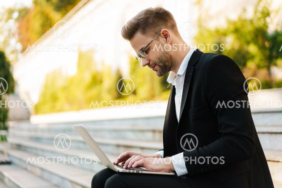 Handsome focused businessman working with laptop while...