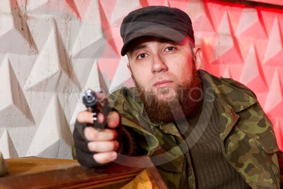 terrorist with a gun in the stroma of a dilapidated...