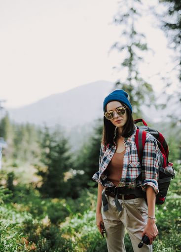 Portrait of attractive girl in a hat with a vape and...