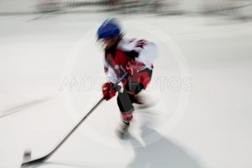 Young hockey player in red dress with blue helmet in...