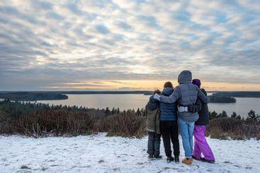 Familj tillsammans i snön på berg och ser ut över vatten.