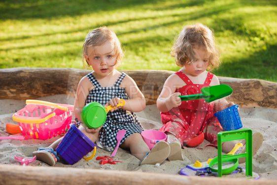 The two little baby girls playing toys in sand