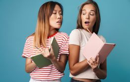 Portrait of young women holding exercise books and peeking