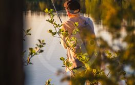 Man is fishing in a small lake in Sweden