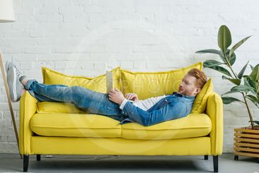 Young man lying on sofa with open laptop