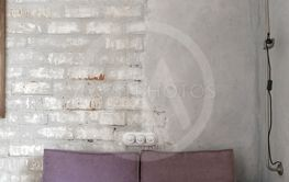 Pink sofa against white brick and plastered wall