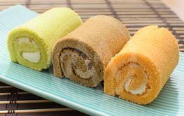 Colorful swiss roll on green dish on bamboo mat