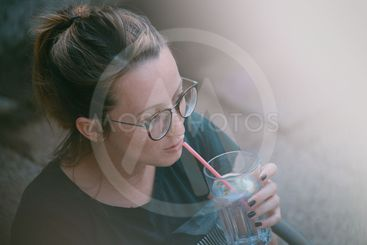 Woman sipping on gin tonic
