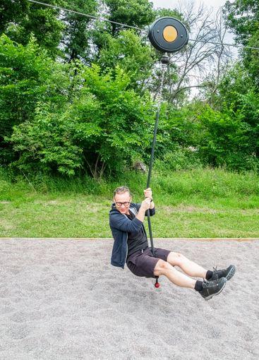 Man med glasögon åker linbana på lekplats i Järfälla.
