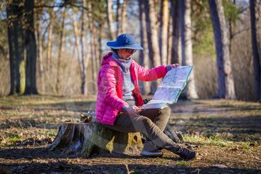 female tourist in the forest looks at a map sitting on a...
