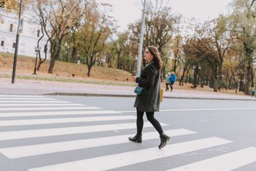 Lady walking towards the park on the pedestrian crossing