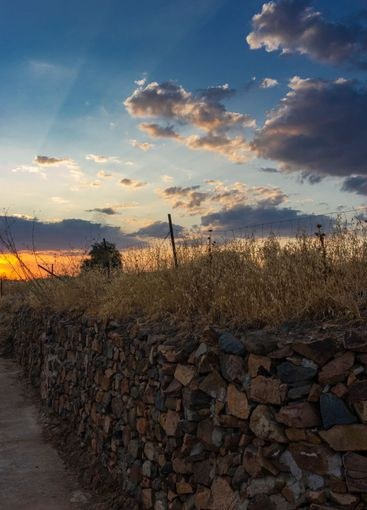 Stone wall in a field in Andalusia with a sunset sky