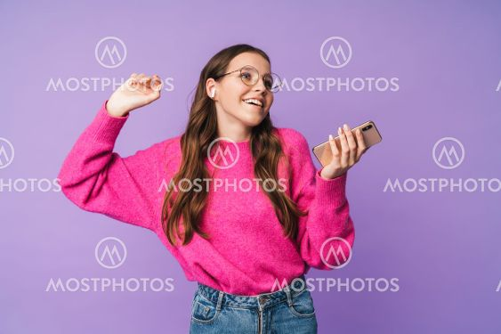Image of young woman wearing earbuds smiling and holding...
