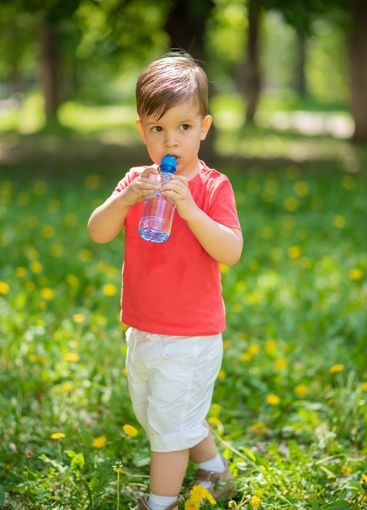 handsome boy drinks clear water from a bottle on a sunny...
