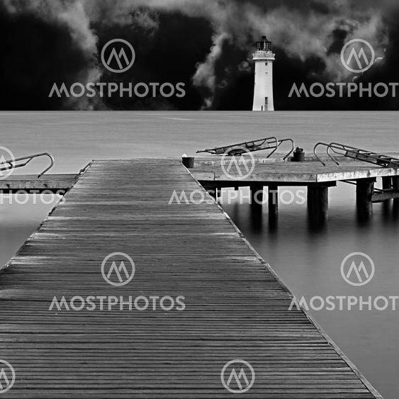 Lange eksponering på træ pier ved daggry med fyr og storm skyer