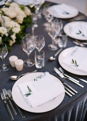 Wedding dinner table reception. White round plates on a...