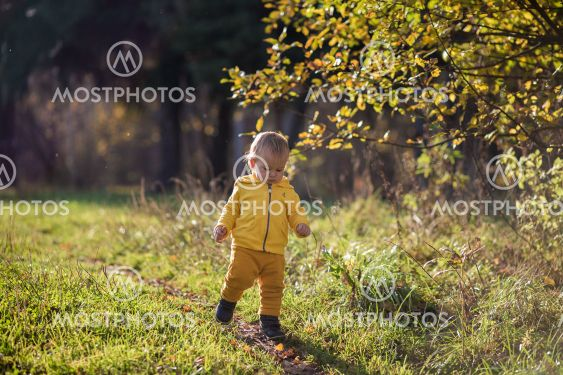 .Toddler todler in a yellow jacket learns to walk in an...