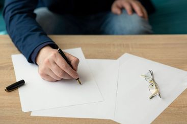 Businessman writes a letter or signs a document