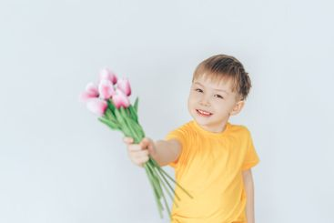 Boy holding a bouquet with tulips in their hands....