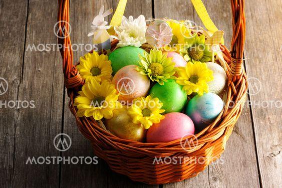 Värillisiä pääsiäismunia korissa