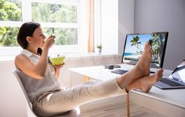 Businesswoman Watching Video On Computer And Eating Food