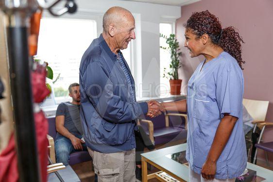 Sköteska hämtar patient i väntrum