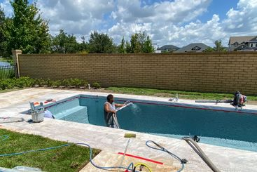 Workers from a pool finishing company spraying plaster...