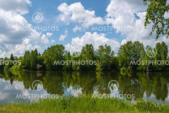 Reflection of green trees and blue sky with clouds in...