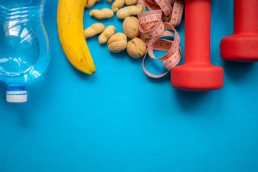 Banana, nuts, water, measuring tape and dumbbells