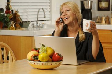 Woman in Kitchen on Cell Phone & Laptop