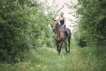 Young woman ridding on a horse