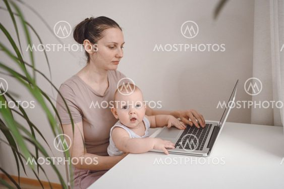 Young mother work studying from home with laptop...