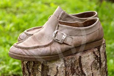 Old Vintage leather Shoes grey colour on green background