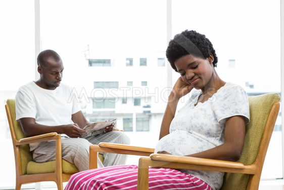 Pregnant couple sitting on chair