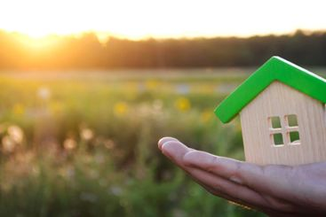 Wooden house in the hands in the sunset background. Real...