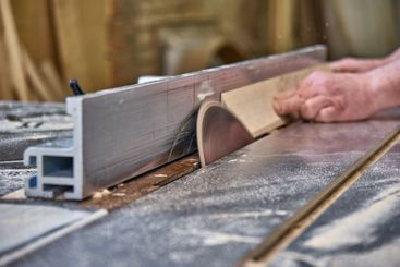 Joinery. Carpenter cutting wood with table saw