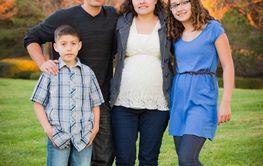 Hispanic Pregnant Family Portrait Against Fall Colored...